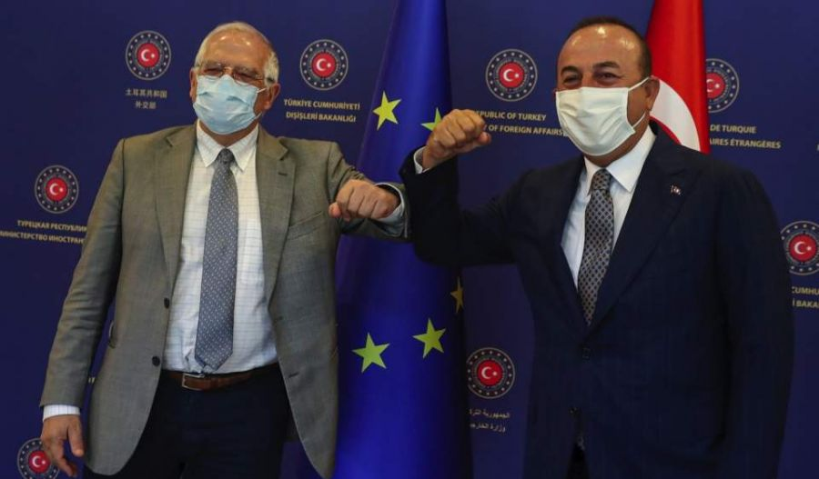 Turkey's Foreign Minister Mevlut Cavusoglu (r) and Josep Borrell Fontelles, High Representative and Vice-President of the European Commission, greet each other by using their elbows before their talks
